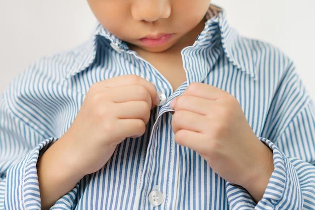 Conceito de desenvolvimento infantil: feche as mãos de um menino de jardim de infância aprendendo a se vestir, abotoando sua camisa azul listrada. montessori habilidades práticas da vida - cuidado de si, educação infantil.