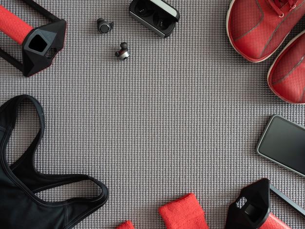 Conceito de desgaste de esporte vista superior com roupa de ginástica, tênis, smartphone, fones de ouvido sem fio verdadeiros e acessórios de corrida de esporte no fundo de esteira de ioga.