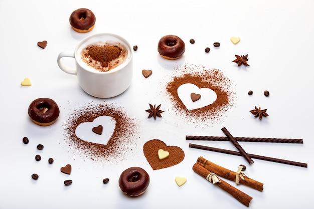 Conceito de design de dia dos namorados com cacau em pó em forma de coração, donuts de chocolate e cappuccino