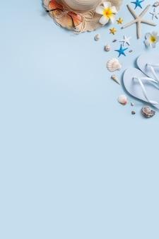 Conceito de design de fundo de praia de verão. vista superior da viagem de férias com conchas, chapéu, chinelo sobre fundo azul.