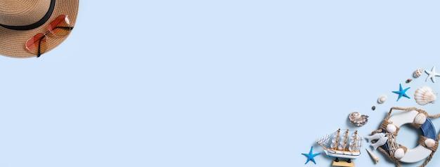 Conceito de design de fundo de praia de verão. vista superior da viagem de férias com conchas, chapéu e óculos de sol sobre fundo azul.