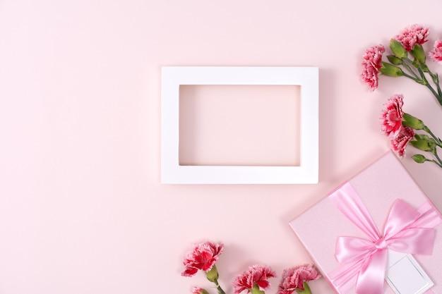 Conceito de design de fundo de saudação de feriado do dia das mães com buquê de cravos em fundo rosa