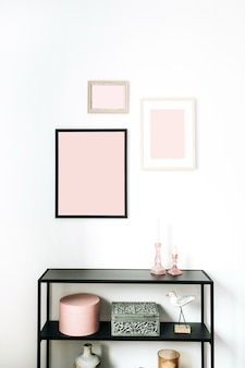 Conceito de design de interiores nórdico escandinavo minimalista rosa moderno decorado com molduras de fotos simuladas, estatueta de pássaro, rack em branco.