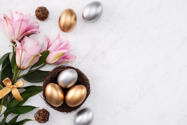 Conceito de design de ovos de páscoa de ouro e prata no ninho com flor de lírio rosa em fundo de mesa de mármore branco brilhante.