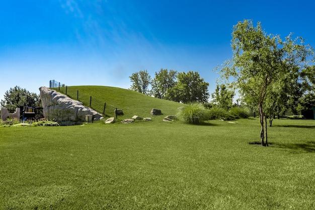 Conceito de design de paisagem. área de parque bem cuidada com grama cortada em uma encosta de estrutura de rocha natural, árvores jovens e parquinho infantil no fundo no dia de verão