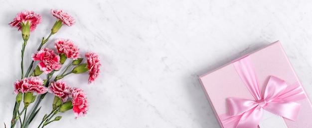 Conceito de design de presente de saudação de feriado de dia das mães com buquê de cravos em fundo de mármore branco