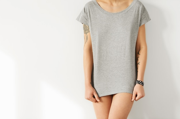 Conceito de design de t-shirt. foto recortada de jovem modelo europeu, vestida com camiseta casual cinza longa