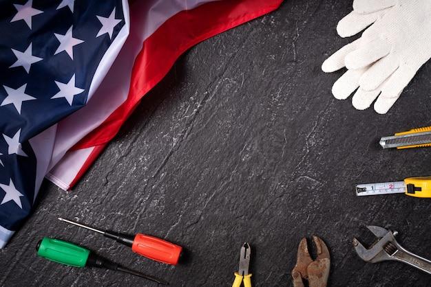 Conceito de design de vista superior do american labor day com ferramentas de trabalho no fundo da mesa de ardósia.