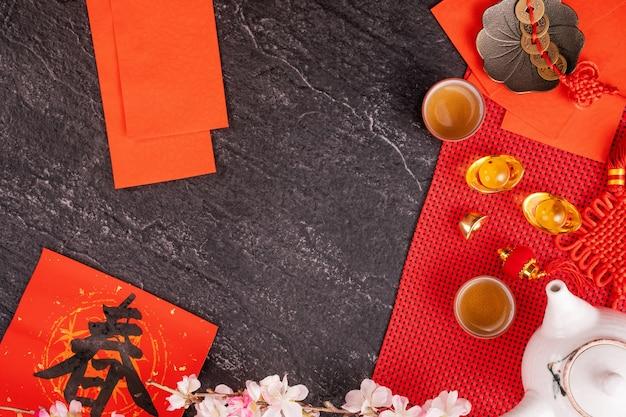 Conceito de design do ano lunar chinês de janeiro novo - acessórios festivos, envelopes vermelhos (ang pow, hong bao), vista de cima, disposição plana, acima. a palavra 'chun' significa próxima primavera.