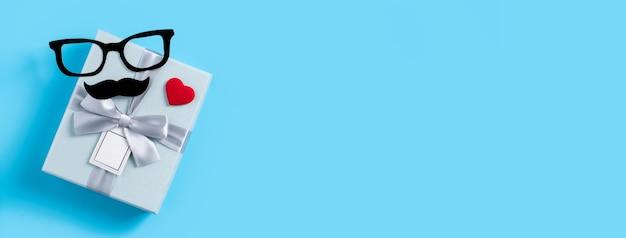 Conceito de design do fundo do dia dos pais. vista superior de ideias de layout de decoração de papel colorido com caixa de presente em fundo de mesa azul com espaço de cópia.