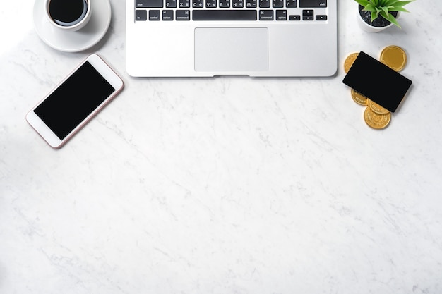 Conceito de design financeiro de negócios, vista de mesa de escritório em mármore branco com telefone inteligente, maquete de cartão de crédito, moedas, laptop, lay-out, espaço de cópia