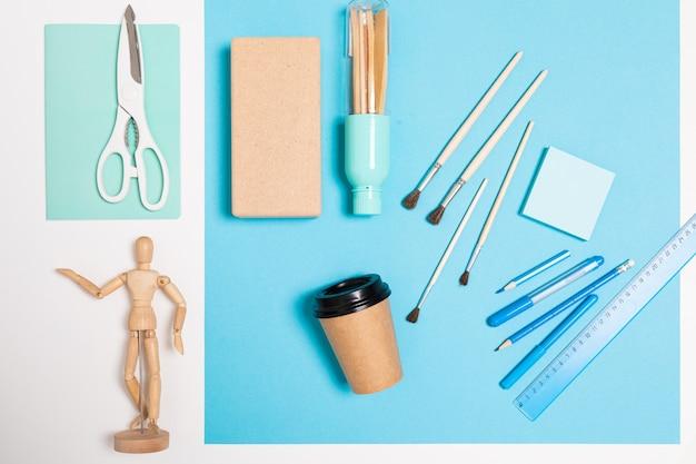 Conceito de design. suprimentos para pintura em uma mesa azul