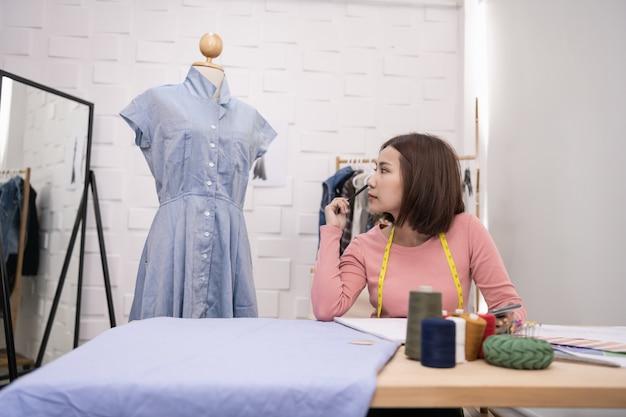Conceito de designer. a costureira está projetando um vestido de noite no quarto
