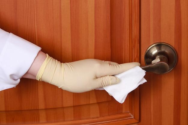 Conceito de desinfecção de superfícies contra bactérias ou vírus, mão com luva, limpeza da maçaneta da porta com pano úmido desinfetante corona vírus, covid 19