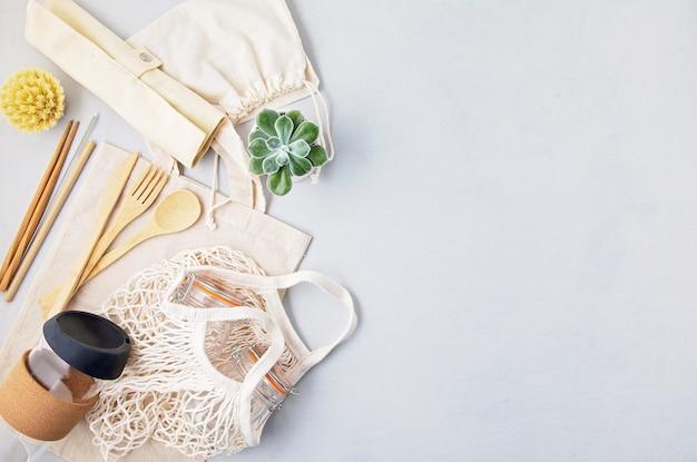 Conceito de desperdício zero. conjunto de talheres de bambu ecológicos, saco de malha de algodão, copo de café reutilizável. compras sustentáveis e éticas, estilo de vida sem plástico. vista de cima, configuração plana.