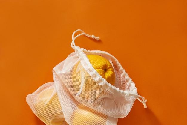 Conceito de desperdício zero. saco ecológico com laranjas. saco costurado de uma cortina velha. o plástico é gratuito e um conceito ecológico. saco ecológico reutilizável para fazer compras.
