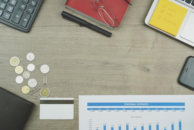 Conceito de despesas pessoais com moeda tailandesa, calculadora, gráfico, laptop, cartão de crédito no fundo da mesa de madeira