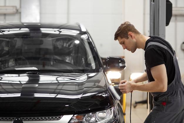 Conceito de detalhamento e polimento do carro. jovem trabalhador profissional de serviço de carro