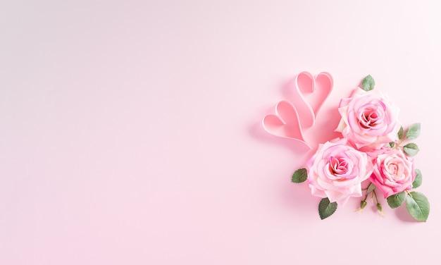 Conceito de dia da mulher feliz. vista superior da flor de rosas com coração em fundo rosa pastel.