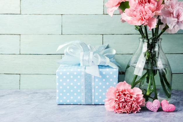Conceito de dia das mães de flores de cravo-de-rosa em garrafa clara e caixa de presente e coração