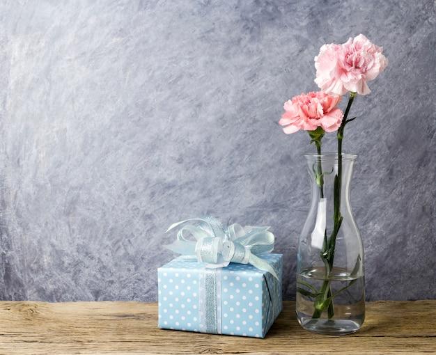 Conceito de dia das mães de flores de cravo-de-rosa em garrafa clara e caixa de presente