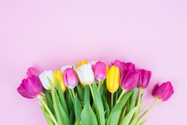 Conceito de dia das mães feliz. foto de alto ângulo de um lindo buquê multicolorido de tulipas isolado em um fundo rosa pastel