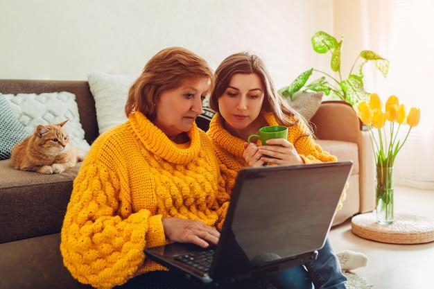 Conceito de dia das mães mãe sênior e sua filha adulta usando laptop, verificando notícias em casa enquanto bebe chá.