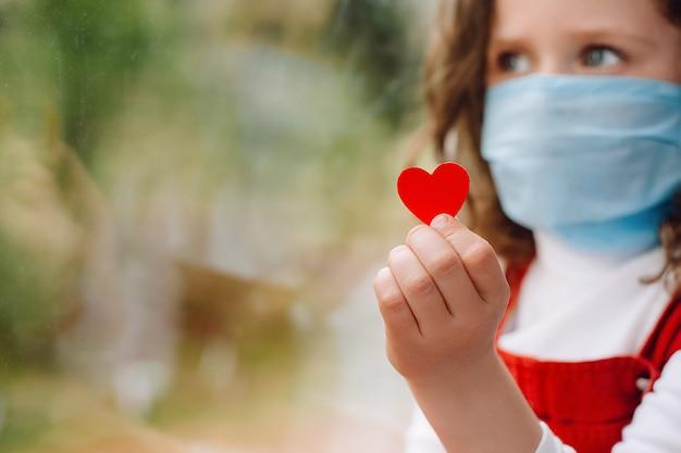 Conceito de dia de enfermeira. menina pequena segurando um pequeno coração vermelho uma maneira de mostrar agradeça a suas enfermeiras agradecendo aos médicos e à equipe médica que trabalham em hospitais durante as pandemias de coronavírus covid-19. foco seletivo