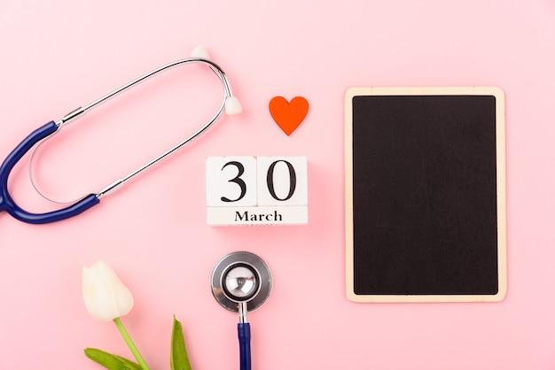 Conceito de dia do médico, estetoscópio médico de equipamento e coração vermelho