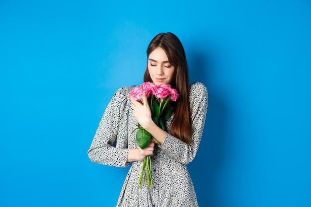 Conceito de dia dos namorados apaixonado e romântico jovem abraçando o buquê de rosas de presente cheirando fl ...