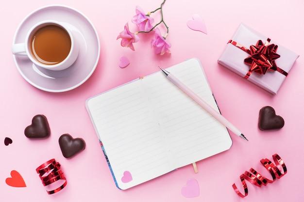 Conceito de dia dos namorados. bombons de chocolate e café, corações em um fundo rosa. espaço de cópia plana leigos. cartão e presente.