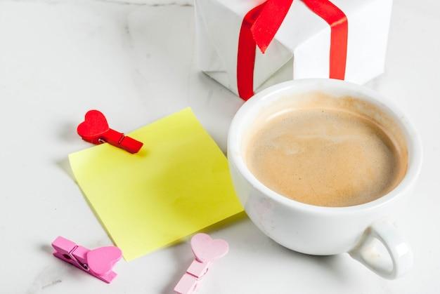Conceito de dia dos namorados, caixa de presente com fita vermelha, caneca de café, nota de papel em branco para parabéns com pinos em forma de coração, branco, copyspace vista superior