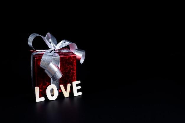Conceito de dia dos namorados caixa de presente e palavra de letras de madeira