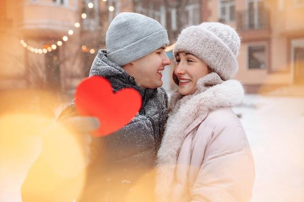 Conceito de dia dos namorados, casal apaixonado beija e abraça em um parque de inverno nevado. jovem segura um coração de papel vermelho enquanto celebra o dia dos namorados com a namorada. um casal se sentindo aquecido.