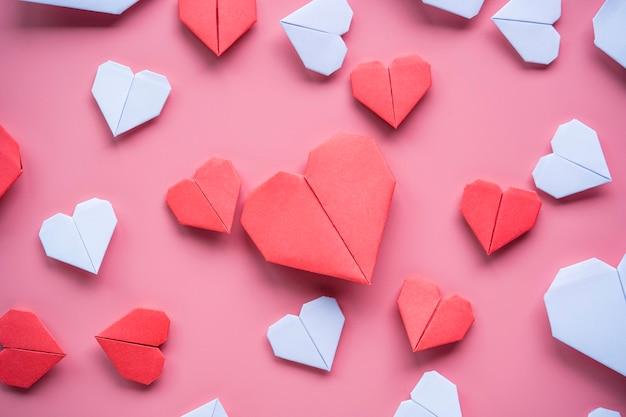 Conceito de dia dos namorados, coração branco e vermelho sobre fundo rosa.