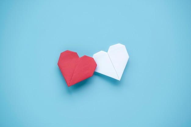 Conceito de dia dos namorados, coração vermelho e branco sobre fundo azul.