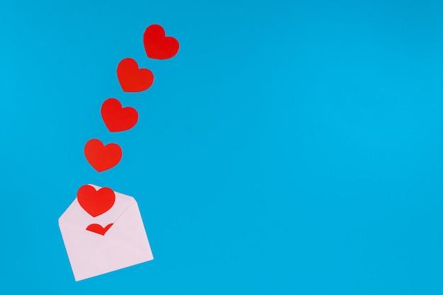 Conceito de dia dos namorados. coração vermelho sai de um envelope rosa claro