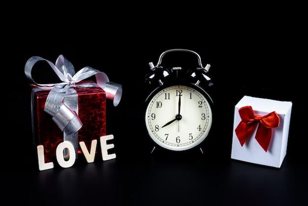 Conceito de dia dos namorados despertador com caixa de presente e palavra de letras de madeira