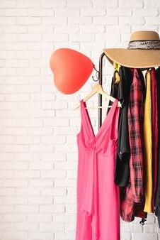 Conceito de dia dos namorados e dia das mulheres. cremalheira de roupas queda de várias roupas femininas e vestido rosa para namoro