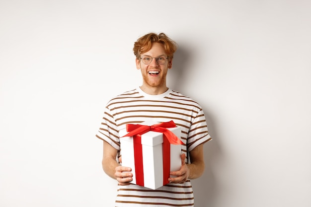 Conceito de dia dos namorados e feriados. jovem alegre segurando a caixa de presente e sorrindo agradecido, recebendo presentes, em pé sobre um fundo branco.