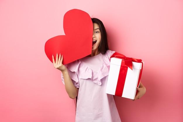 Conceito de dia dos namorados. feliz jovem asiática segurando presentes românticos, cartão de coração vermelho do amante e caixa de presente, olhando espantado com a câmera, em pé no vestido em fundo rosa.