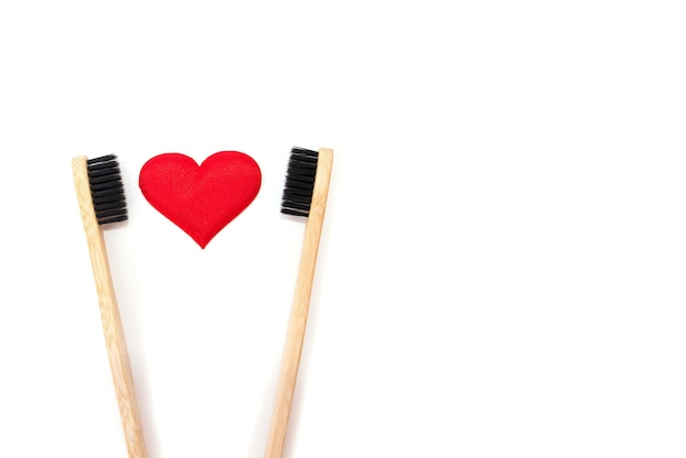 Conceito de dia dos namorados. foto de close up de duas escovas de dente de madeira ecológicas de bambu com cerdas pretas e brancas e coração vermelho, fundo branco isolado com espaço em branco vazio