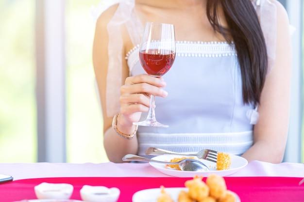 Conceito de dia dos namorados, jovem asiática sentada à mesa de comida com taças de vinho e buquê de vinho de rosas vermelhas e rosa e esperando por seu homem no fundo do restaurante