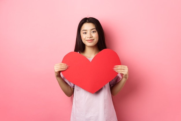 Conceito de dia dos namorados. linda garota asiática adolescente mostrando cartão de grande coração vermelho, se apaixonando, indo a um encontro romântico no vestido, sorrindo com ternura para a câmera, fundo rosa.