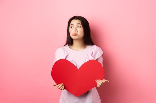 Conceito de dia dos namorados. menina asiática adolescente solitária sonhando com o amor, sentindo-se triste e solitária no dia dos namorados, olhando para o lado com pena, segurando um grande coração vermelho, fundo rosa.