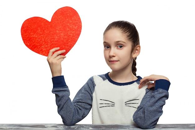 Conceito de dia dos namorados - menina com coração vermelho. isolado no modelo feminino de fundo branco do estúdio
