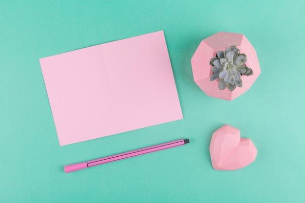 Conceito de dia dos namorados, minimalismo. cartão-de-rosa, caneta, coração, suculenta de flor em um fundo de papel verde menta.