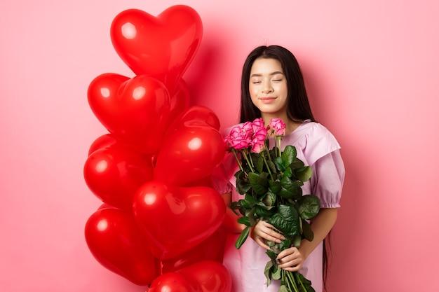 Conceito de dia dos namorados. romântica adolescente asiática sonhando com amor ou encontro, feche os olhos e sorria, segurando flores do amante, receba um buquê de rosas e balões de coração vermelho, fundo rosa.