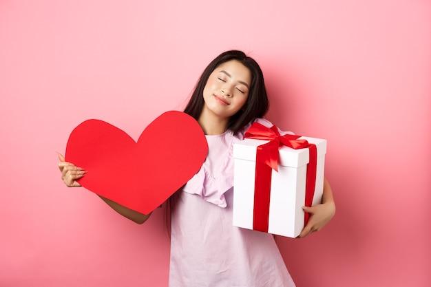 Conceito de dia dos namorados. romântica e terna menina adolescente asiática sorrindo, feche os olhos e sonhadora com presentes de amante, segurando o presente e grande coração vermelho recorte, fundo rosa.