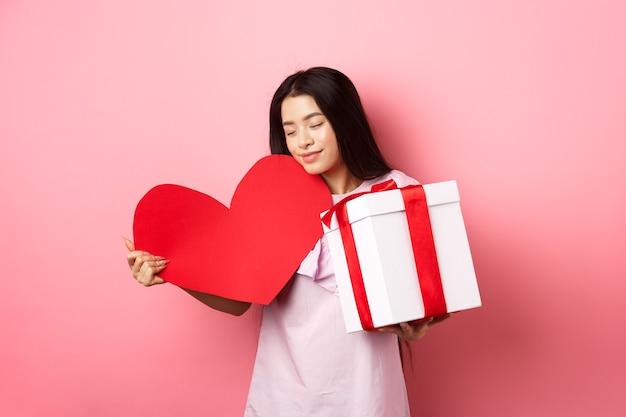 Conceito de dia dos namorados. romântica menina adolescente asiática recebe presentes no dia branco do amante, abraçando o cartão de grande coração vermelho e presente na caixa, sorrindo sensual, fundo rosa.